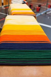 Die verschiedenfarbigen Kordeln zeigen die Graduierung der Capoeiristas an. Die Kordeln liegen der Reihenfolge nach sortiert nebeneinander auf einem Tisch.