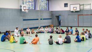 """Die Schülerinnen und Schüler bilden einen Sitz-Kreis auf dem Turnhallen-Boden. Der Kreis ist ein wichtiges Symbol in der Capoeira. Wenn zwei Capoeiristas miteinander spielen, tun sie dies in einem Kreis, der sogenannten """"Roda"""", der aus den zuschauenden Capoeiristas gebildet wird."""