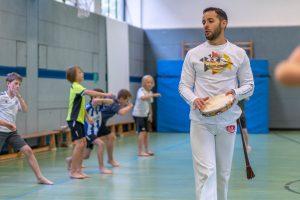 Schüler und Schülerinnen trainieren Capoeira-Bewegungen. Instrutor Cao, der Trainer, gibt den Takt mit einem Pandeiro - einem Tambourin - vor.