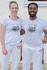 Lila Sax dos Santos Gomes steht neben Cristiano Rozendo Dos Santos. Sie tragen die typische weiße Capoeira-Kleidung und lächeln in die Kamera.